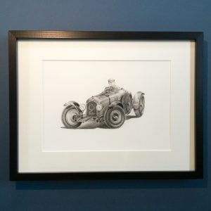 An A4 framed classic car print featuring Nuvolari driving Alfa Romeo. Framed in dark black wood.